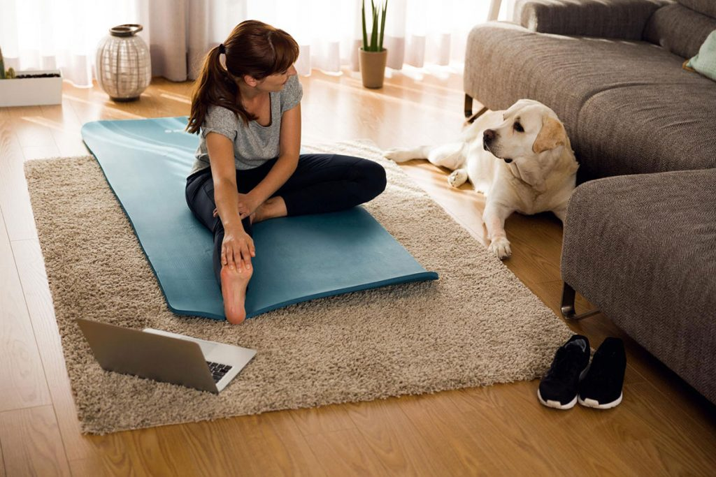 Woman stretches in living room with dog.