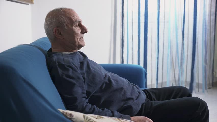 Senior man sitting in a blue chair.